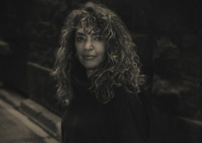Image of Ilana Rose in Black and sepia tone standing on a footpath